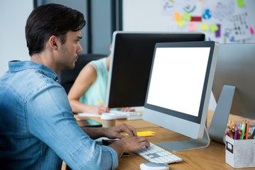 Male graphic designer using graphics tablet at desk