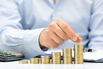 Male hand putting money coin stack growing business, saving money concept.