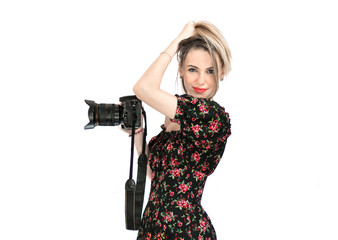 The girl photographer on a white background in a beautiful dress with camera