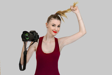 The girl photographer in shirt posing on a gray background with a camera