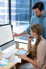 Graphic designer working at desk with colleague