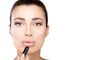 Gorgeous beauty model applying lipstick