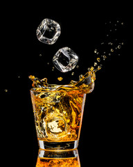 Fototapete - Glass of whiskey with splash on black background
