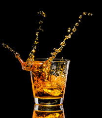 Wall Mural - Glass of whiskey with splash on black background