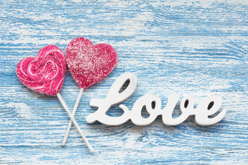 Candy heart with 3D text LOVE on a wooden background