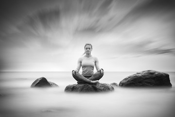Woman lotus position sitting on a stone in the sea and practicing yoga.