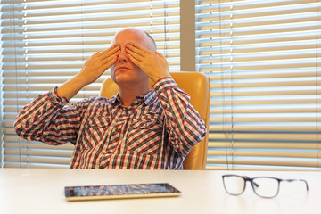 middle age  practicing yoga for eyes in office - break