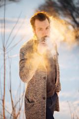 The young guy on the street smoking vape, street fashion with vape steam,vapor e-cigarette