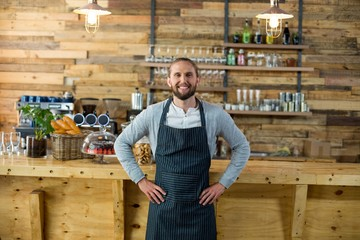 Portrait of waiter standing with hands on hip at counter
