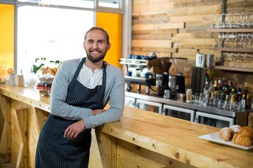Portrait of smiling waiter leaning at counter