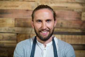 Portrait of smiling waiter standing against wooden wall