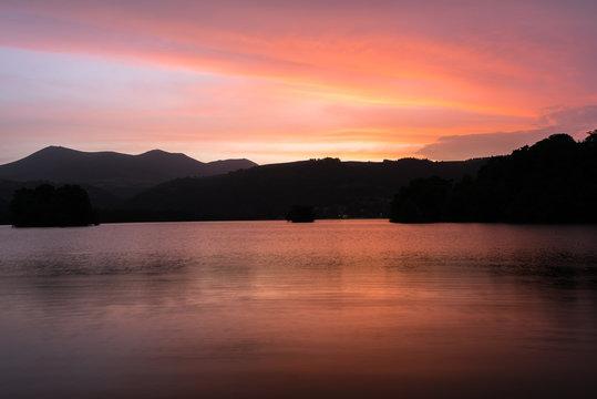 Coucher de soleil en Auvergne autour du Lac Chambon. Nuages et reflets oranges, roses