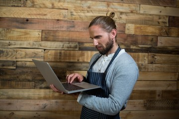 Attentive waiter using laptop against wooden wall