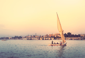 Felucca at sunset - travel on sail vessel on the Nile river, romantic cruise and adventure in Egypt. Traditional egyptian sailboat on horizon. Skyline of Luxor on riverside.
