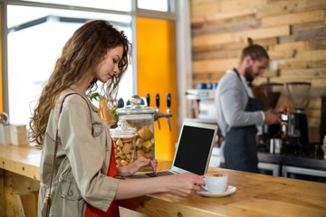 Woman standing at counter and using laptop while having coffee