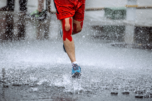 Fototapete male athlete with tape on his knees running through a puddle of water, splashes and drops around feet