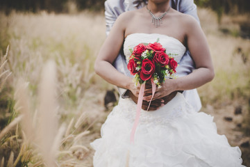 Bride holds a wedding bouquet in hands, the groom hugs her from