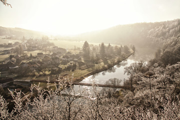 Winter sunny and foggy valley with the wide river