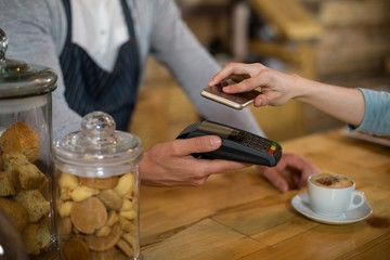 Papiers peints Bar Woman paying bill through smartphone using NFC technology