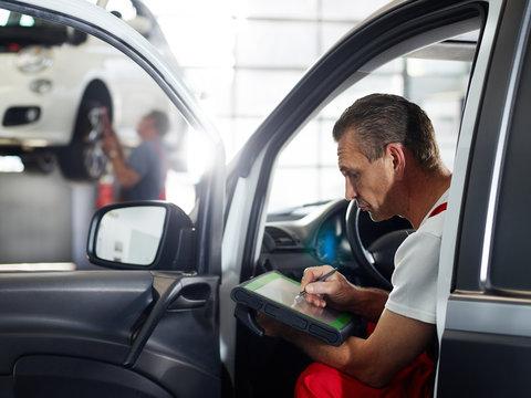 Mechanic checks the engine of a car