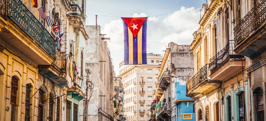Wall Murals Havana A cuban flag with holes waves over a street in Central Havana. La Habana, as the locals call it, is the capital city of Cuba