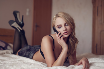 Sexy blonde woman calling on bed by phone indoor