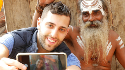 Tourist taking a selfie with Sadhu - Holy Man, in Varanasi, India