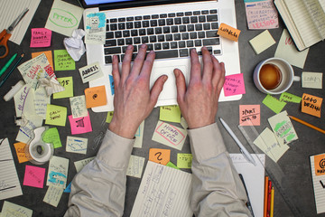Top view on man working on laptop computer with post it notes all around his office table.