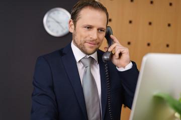 mitarbeiter an der hotelrezeption gibt auskunft am telefon