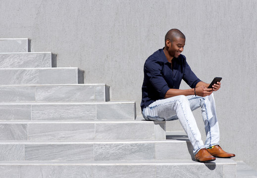 young african american man sitting on steps using tablet