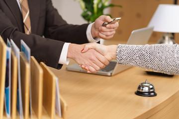 rezeptionist begrüßt eine kundin per handschlag