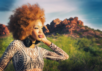 Fashion style shoot with beautiful African American model wearing one-piece, profile view looking to desert.