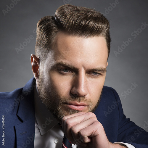 Style hair cut on young brutal man with beard and official