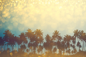 Palm trees on tropical beach, vintage toned and retro color stylized with shiny party glitter overlay effect