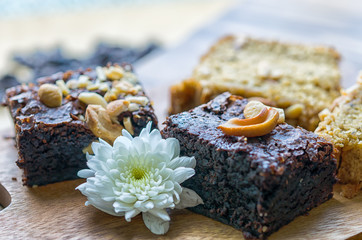 Brownies cake with white flower on wooden chopping block