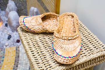 Wicker slippers stand on a wicker basket in the sauna