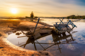 Old abandoned fishing boat wrecked stand on a beech with sunset.