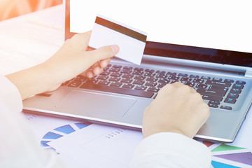 Woman's hands holding a credit card and using smart phone for on
