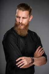 Portrait of serious hipster man with beard and mustashes standing with folded hands looking back and down over shoulder