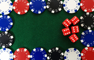 Casino chips and red dice on green background