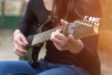 Close up female musician hands playing electric guitar. Lens fla