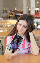 Young beautiful smiling girl with long hair makes selfie