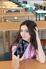 Young beautiful smiling girl with long hair makes selfie and str
