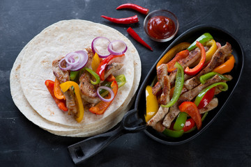 Cast-iron pan and wheat wraps with mexican pork fajitas