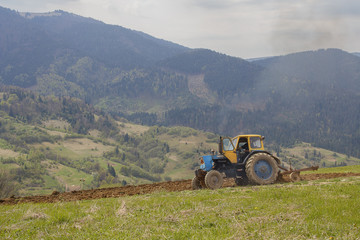 Old tractor plowing the land in the highlands. Agriculture