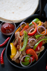 Close-up of a cast-iron frying pan with mexican pork fajitas