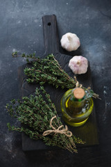 Bunch of fresh thyme with olive oil in a glass bottle and garlic