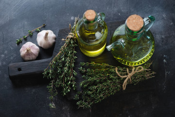 Fresh thyme, olive oil and garlic on a wooden chopping board