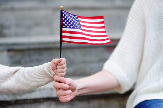 Young woman and little child holding american flag