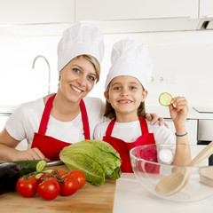 mother and little daughter cooking together with hat apron preparing salad at home kitchen